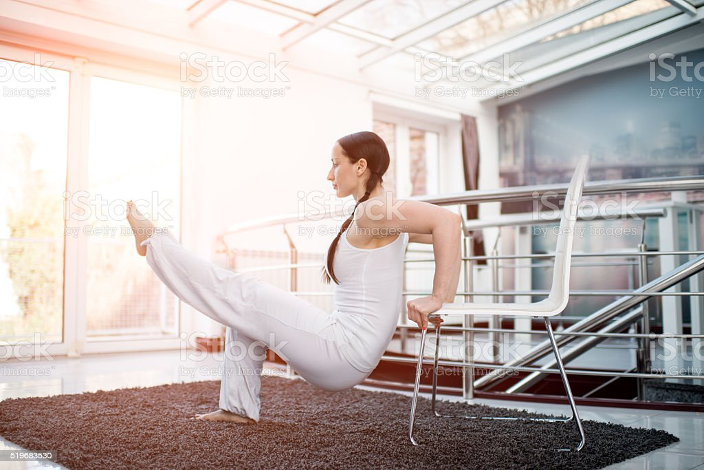Woman in white exercising with a chair stock photo