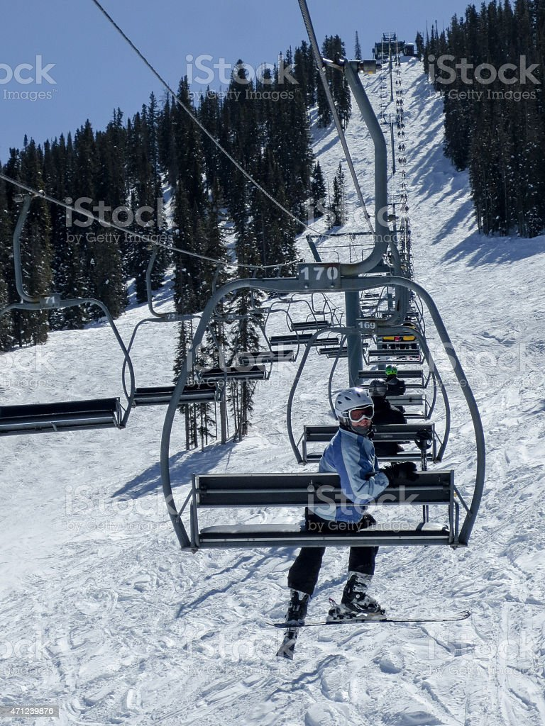 Woman in white helmet on a chair lift at Purgatory stock photo
