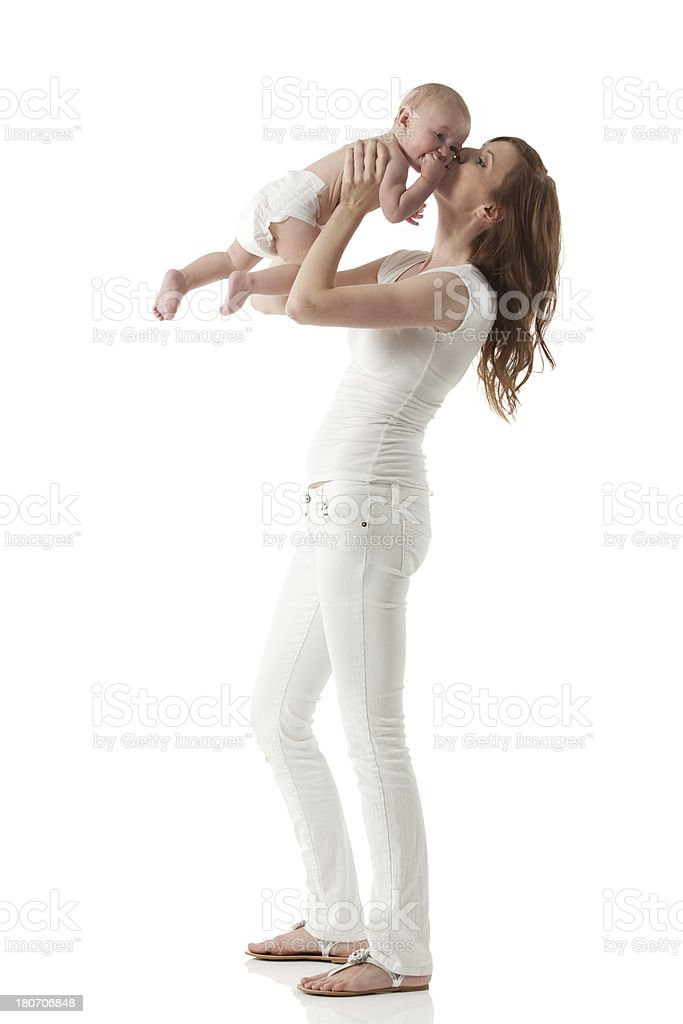 Woman in white holds a baby up to kiss its face royalty-free stock photo