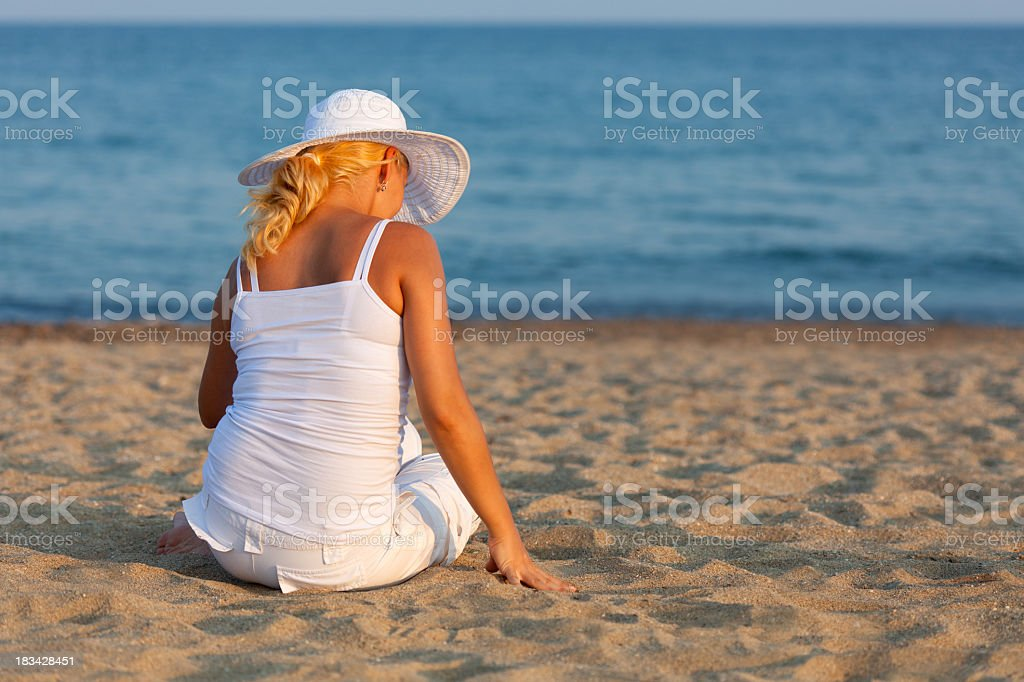Woman in white sitting on sandy beach and relaxing stock photo