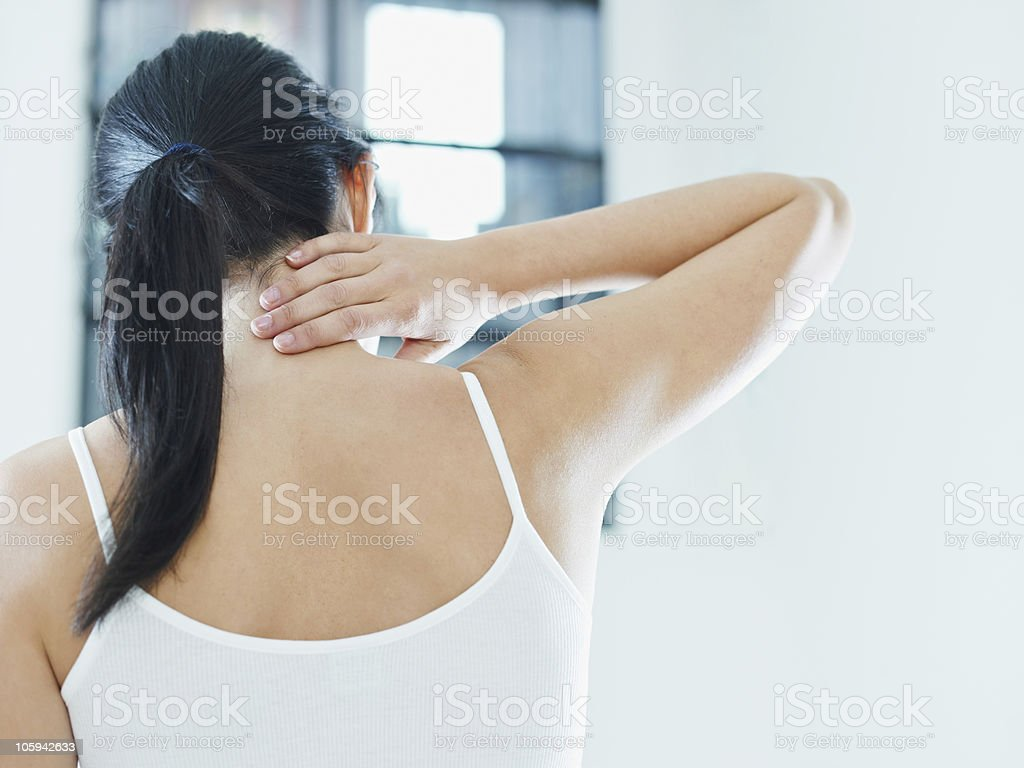 Woman in white touches neck worryingly  stock photo