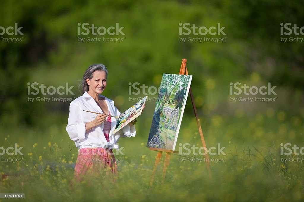 Woman In Wildflower Field Painting On Canvas royalty-free stock photo