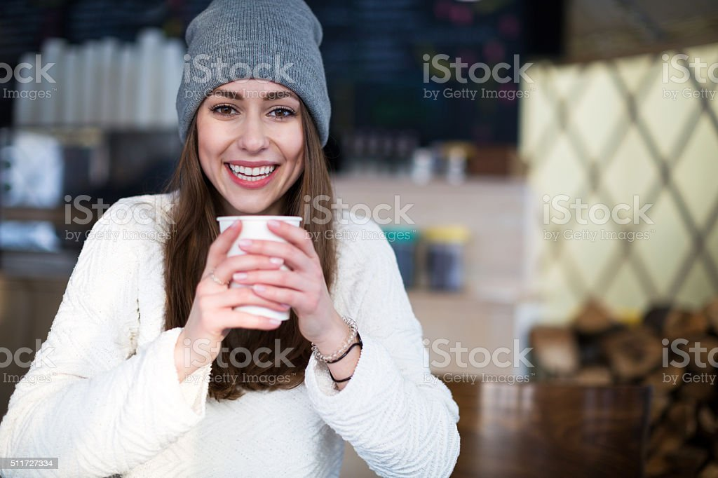 Woman in winter clothes having hot drink stock photo