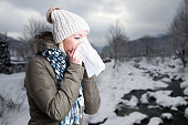 Woman in winter clothes holding a tissue to her nose