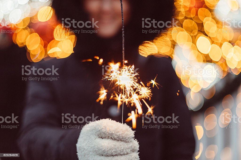 Woman in winter clothing holding christmas sparkler stock photo