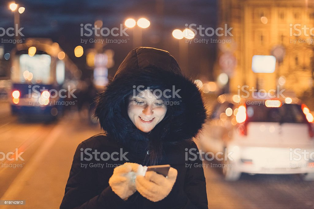 Woman in winter clothing texting at the street stock photo