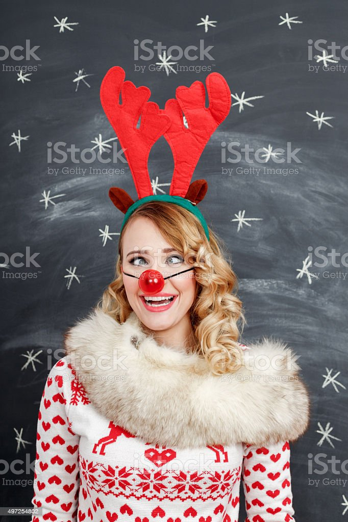 Woman in winter outfit and reindeer antlers headband making squint stock photo