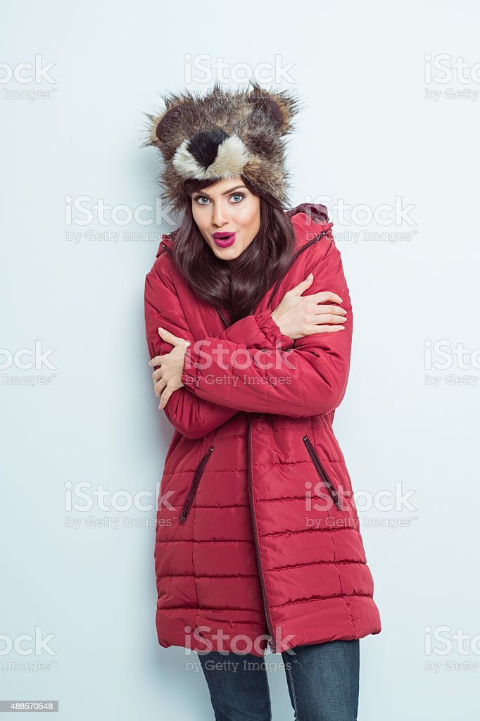 Woman in winter outfit, wearing fur cap and puffer jacket stock photo