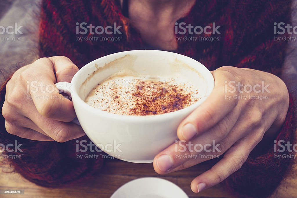 Woman in wool jumper drinking coffee on cold day stock photo