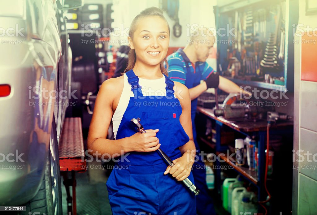Woman in work coveralls working in auto service point stock photo