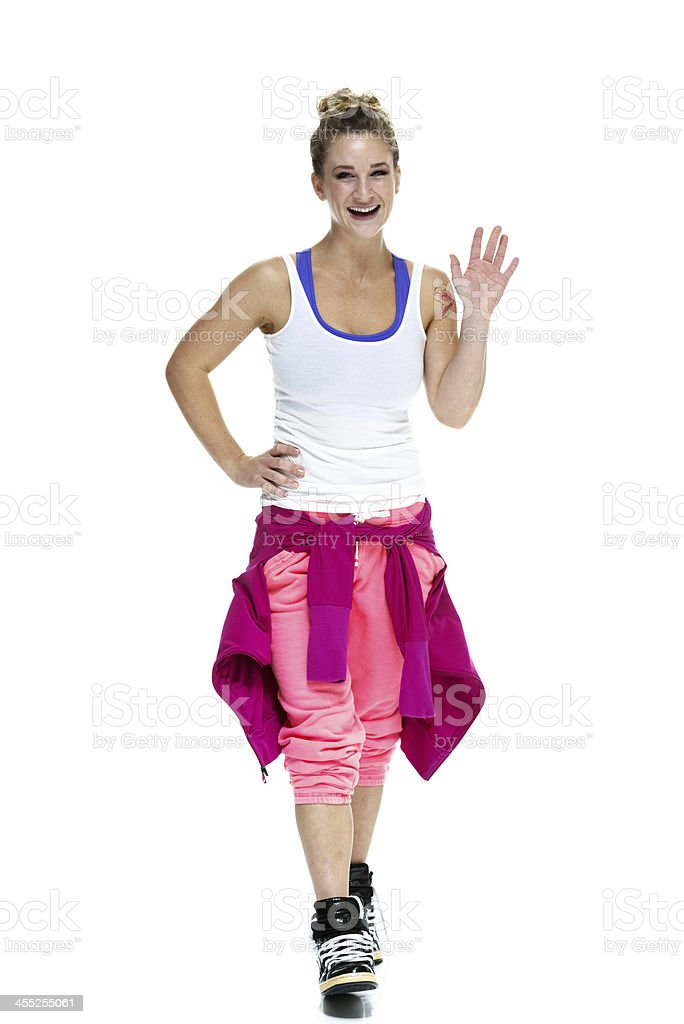 Woman in workout clothing waving hand stock photo
