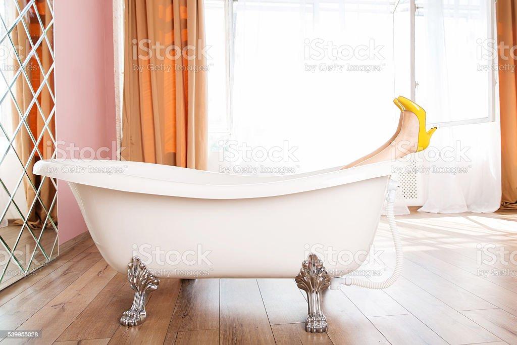 Woman in yellow high heel shoes in bath stock photo