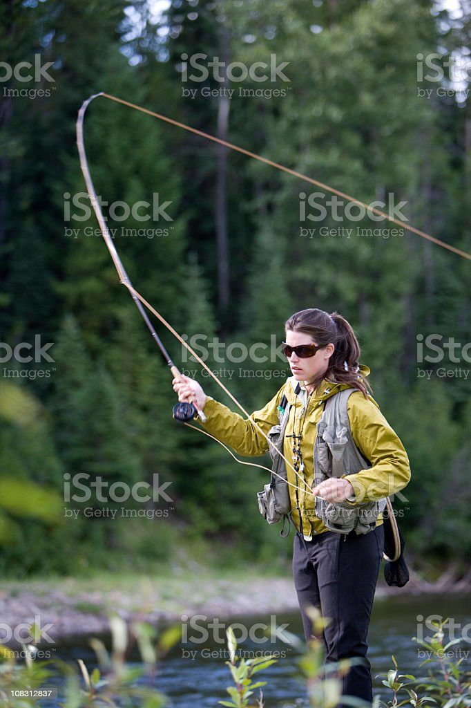 Woman in yellow jacket casting a fly rod in lake stock photo