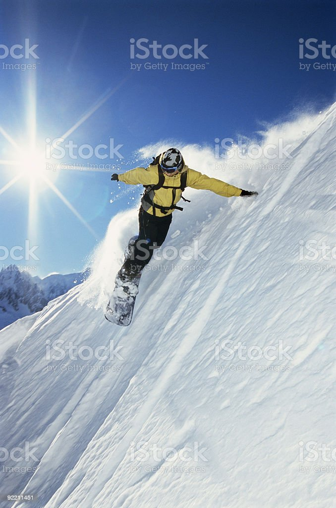 Woman in yellow snowboarding down a mountain royalty-free stock photo