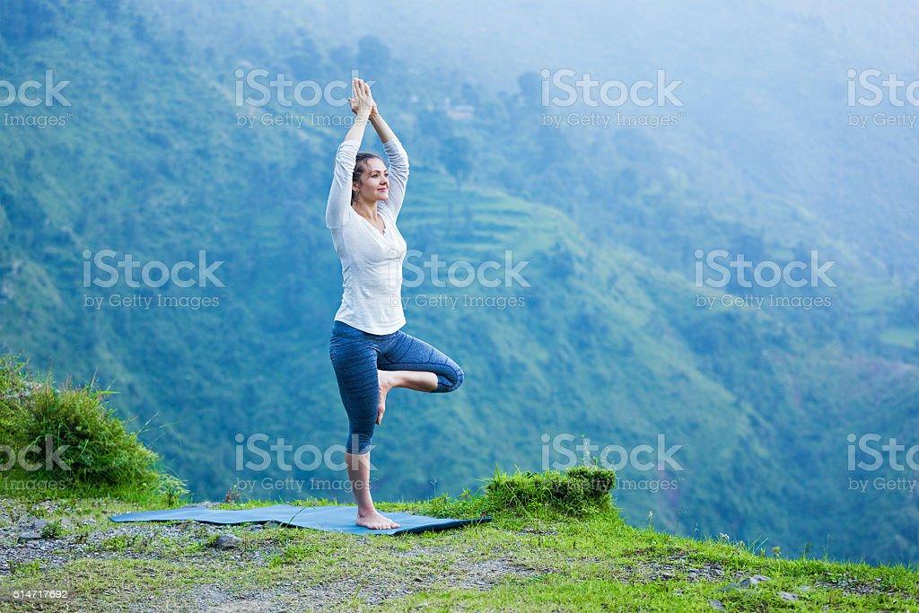 Woman in yoga asana Vrikshasana tree pose outdoors stock photo