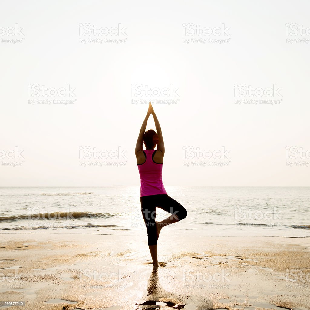 Woman in yoga pose at beach stock photo