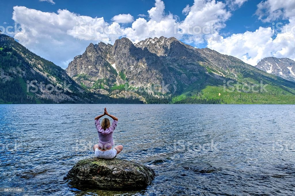Woman in yoga pose meditating by lake and mountains. stock photo