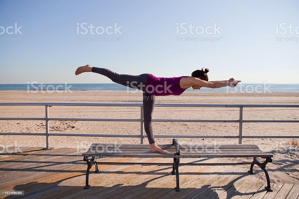 Woman in yoga pose on promenade stock photo