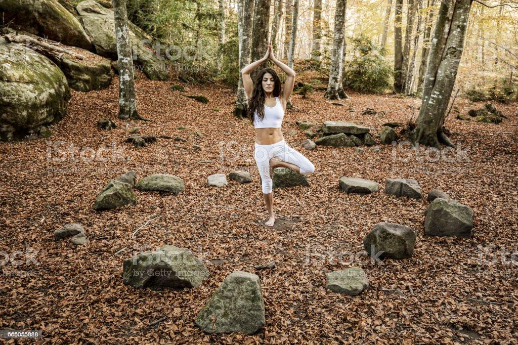 Woman in yoga tree pose inside stone circle stock photo