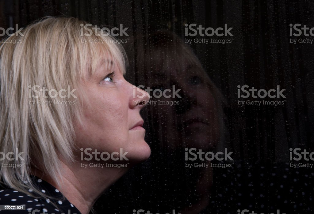 Woman indoors looking out of a window splashed with rain stock photo