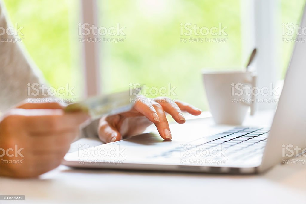 Woman indoors using credit card and laptop. Shopping online. stock photo