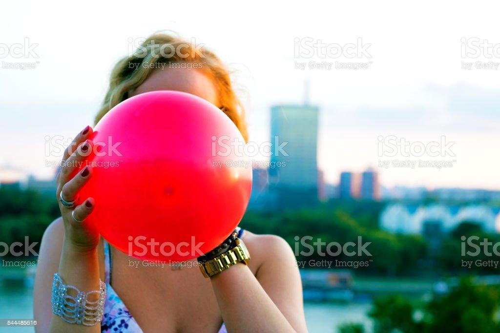 woman inflating balloon stock photo
