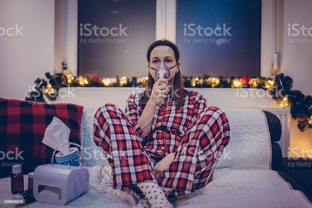 Woman inhaled at home on the bed stock photo