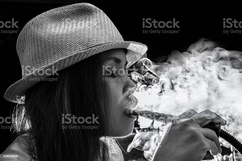 Woman Inhaling from a Hookah stock photo