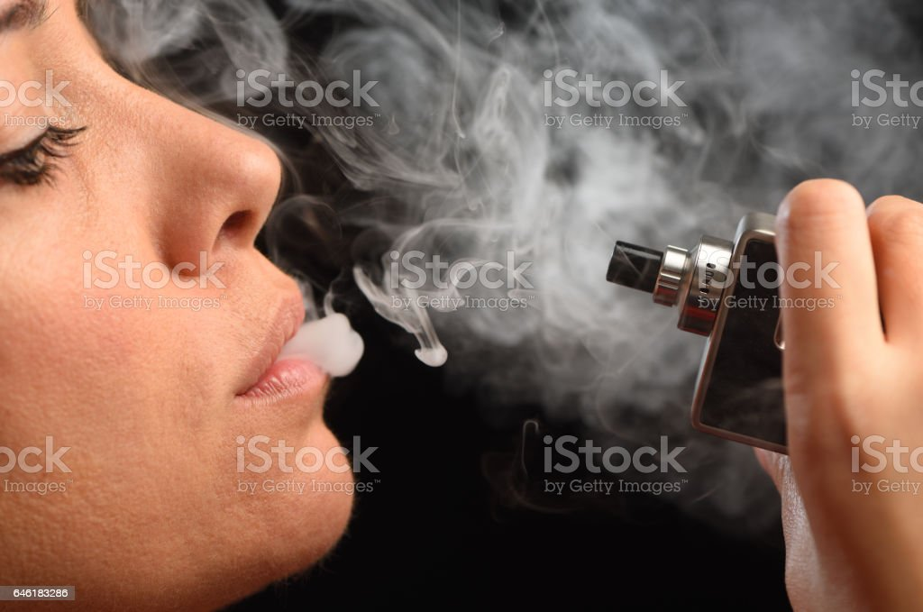 Woman inhaling from an electronic cigarette stock photo
