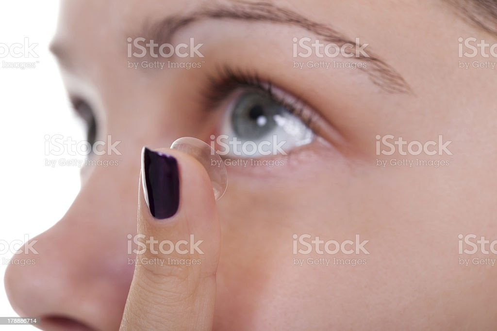 Woman inserting a contact lens stock photo