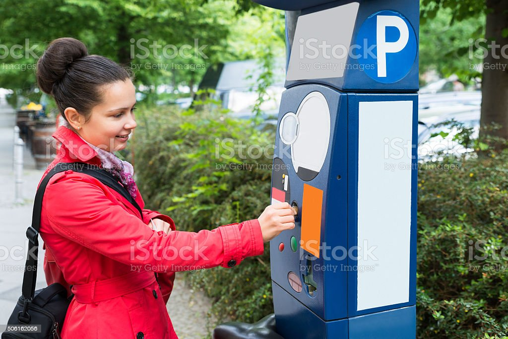 Woman Inserting Coin In Parking Meter stock photo