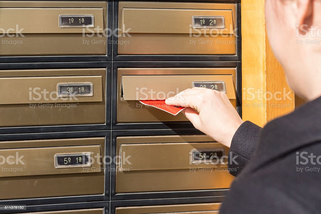 Woman inserting letter in a mailbox stock photo