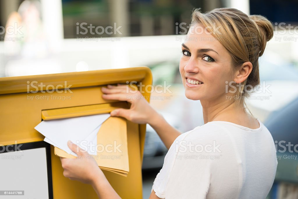 Woman Inserting Letter In Mailbox stock photo