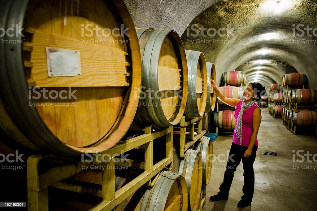 Woman inspecting barrels in cave at Winery Sonoma Napa California stock photo