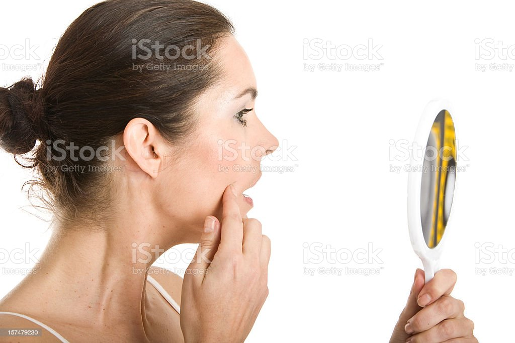 Woman inspecting her skin with a mirror stock photo
