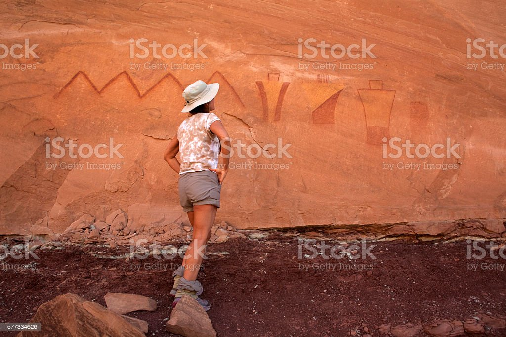 Woman inspects painted pictographs San Raphael Swell desert cliff Utah stock photo