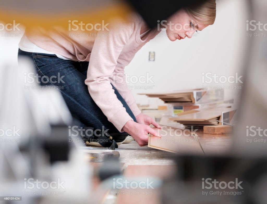 Woman Installing Laminate Flooring stock photo