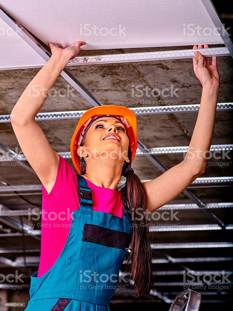 Woman installing suspended ceiling stock photo