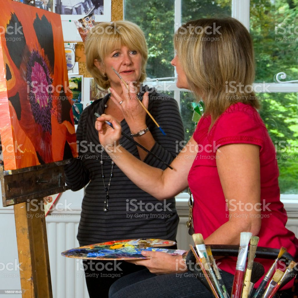 Woman instructing student in a fine arts class stock photo