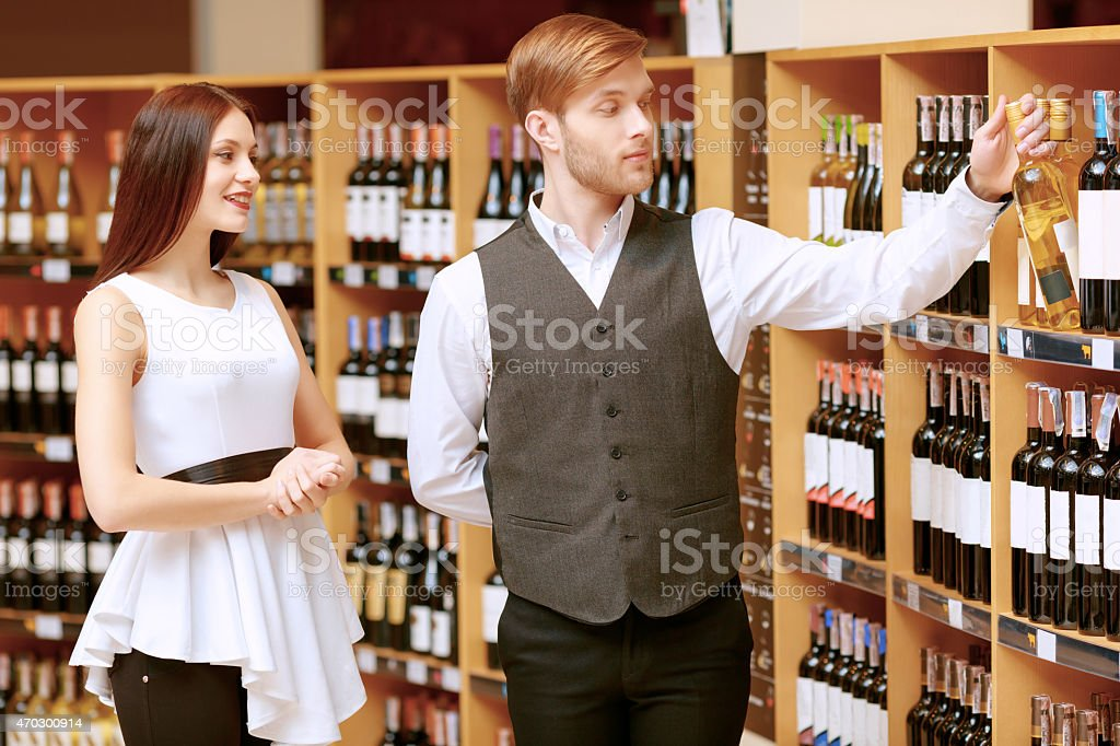 Woman interacts with a sommelier in shop stock photo