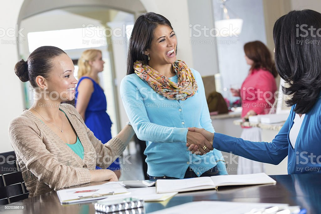 Woman introducing friend to lady at a home party stock photo