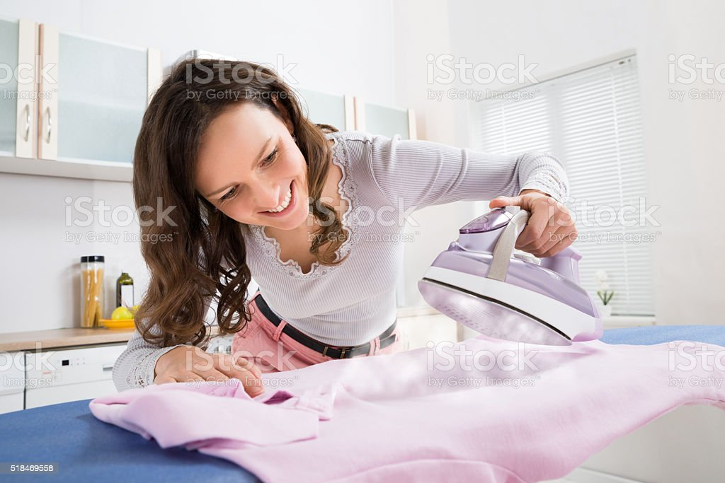 Woman Ironing Cloth With Electric Iron stock photo