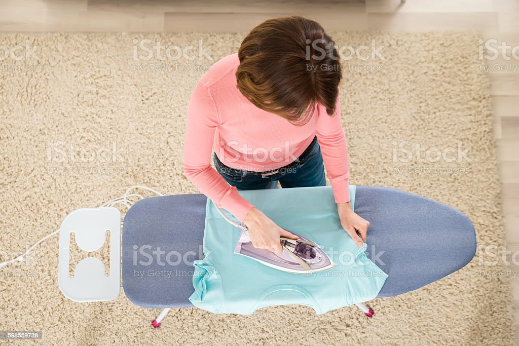 Woman Ironing Clothes With Steam Iron stock photo