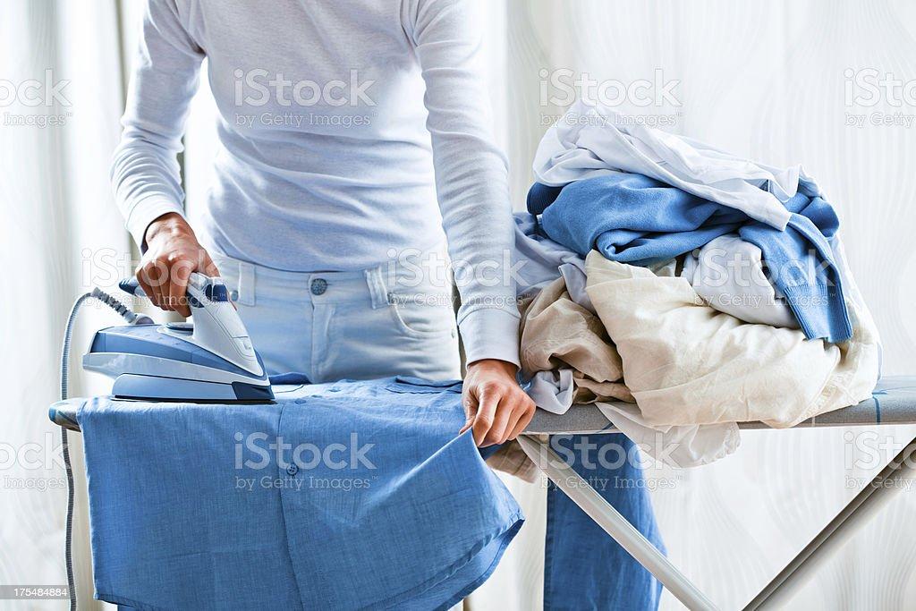 Woman Ironing Shirt Next To Pile Of Laundry stock photo