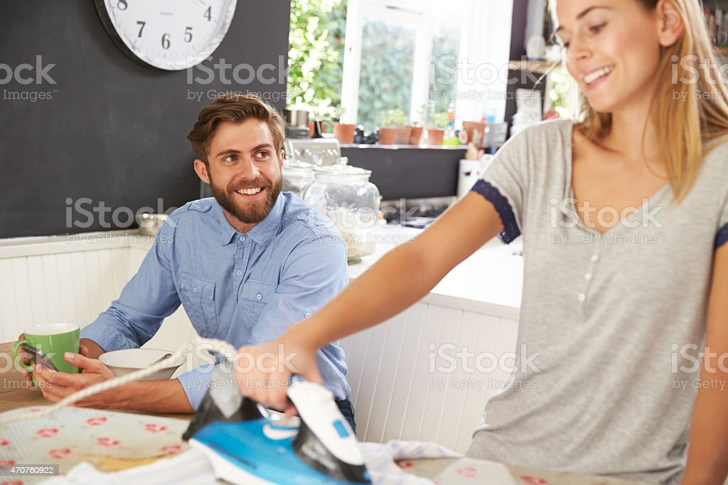 Woman Irons Shirt Whilst Man Eats Breakfast stock photo