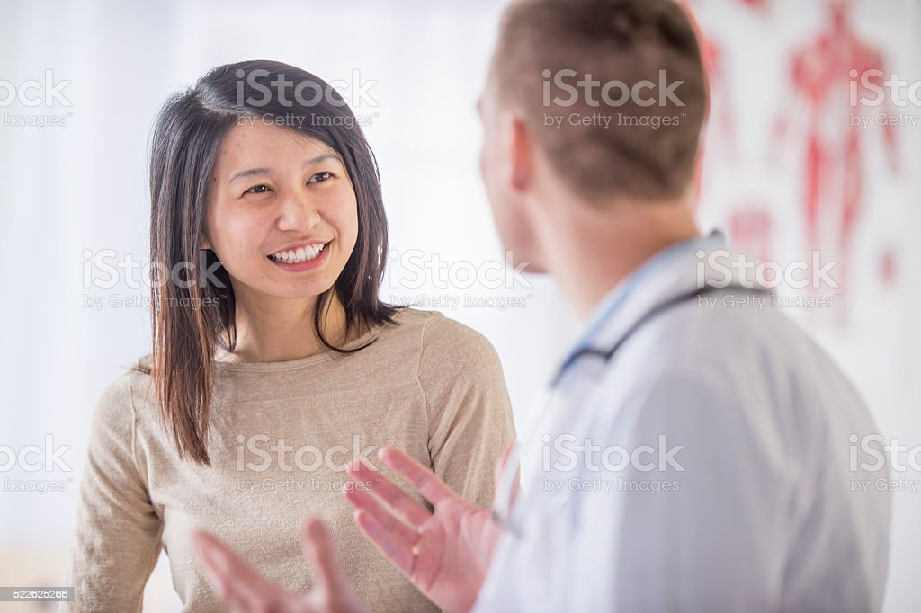 A woman is at the doctor's office and is getting good stock photo