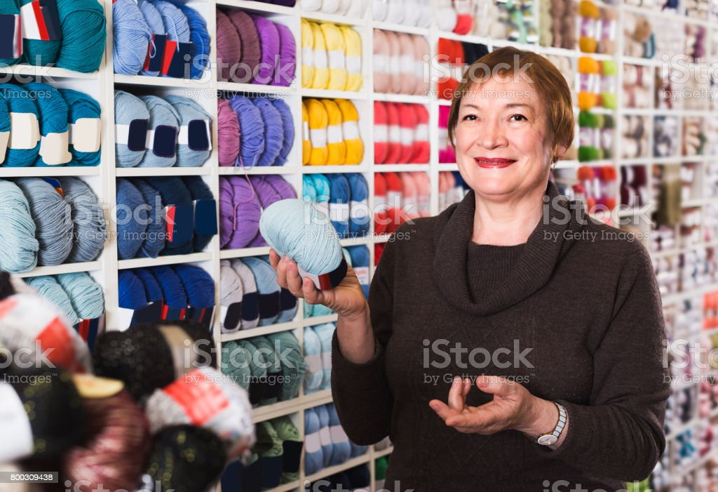 Woman is buying colorful yarn for their hobby stock photo