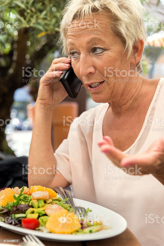 woman is calling during a break in the restaurant stock photo
