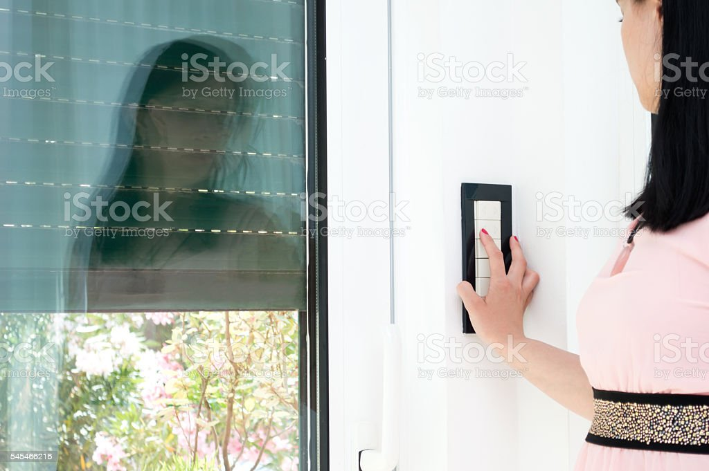 Woman is covering the window by blind stock photo