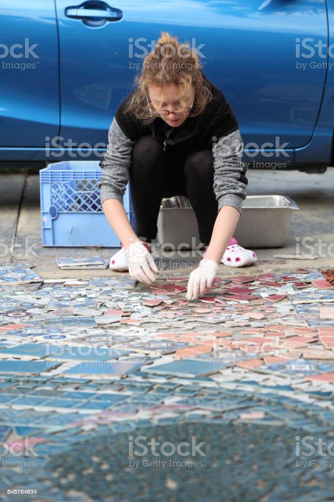 Woman is creating mosaic path. stock photo
